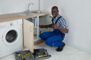 41318065 - young happy african male plumber fixing sink in kitchen